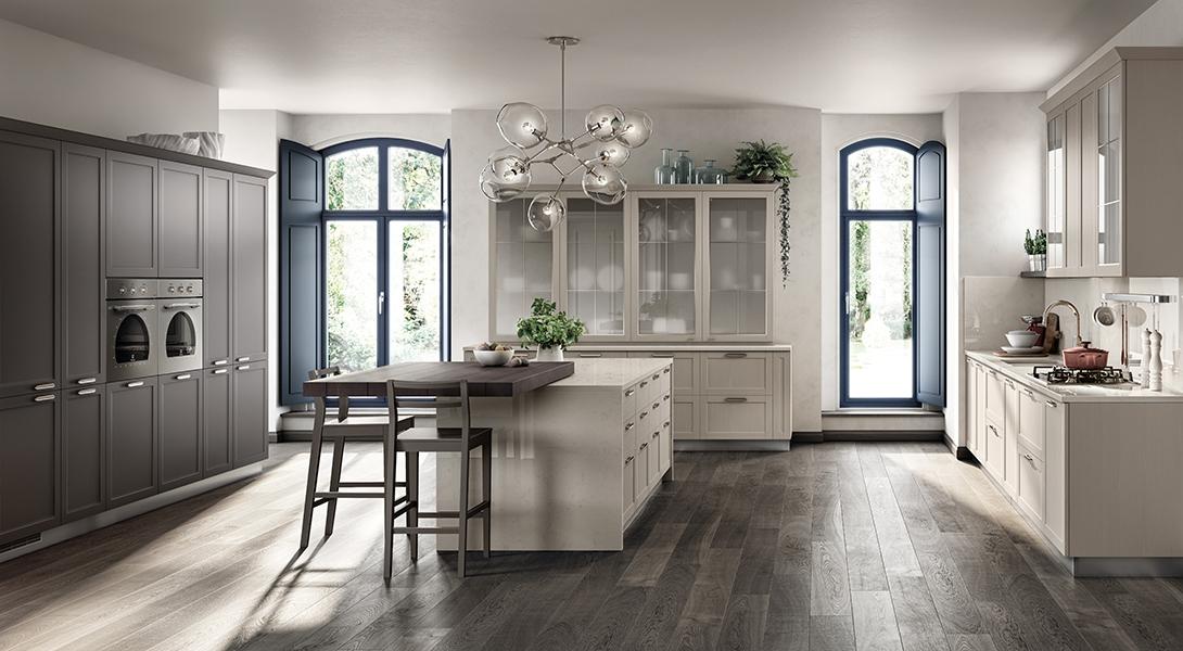 Cocina Carattere Restayling: Composición con cornisa superior en lacado mate Gris Hierro, puertas enchapadas Fresno Cachemira y vitrina con bastidor de cuarterones que se apoya en la encimera.