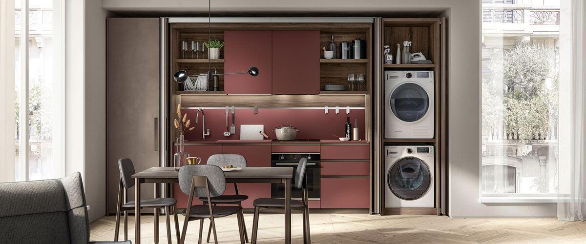 Composición con perfiles tirador y zócalos de la cocina en acabado Bronce combinados con puertas, encimeras y paneles posteriores en Fenix NTM® Rojo Jaipur.